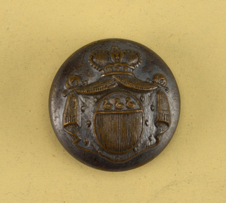 Convex button showing ornament of oval shield with three birds above perpendicular reed, with mantling (ermine?) and drapery held by a crown. On reverse: no marked. Brass back and shank.  On card C