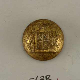Circular, convex button with ornament showing shield with heraldic devices, a man and a griffin as supporters, and a crown. Back and shank of brass.  On card E