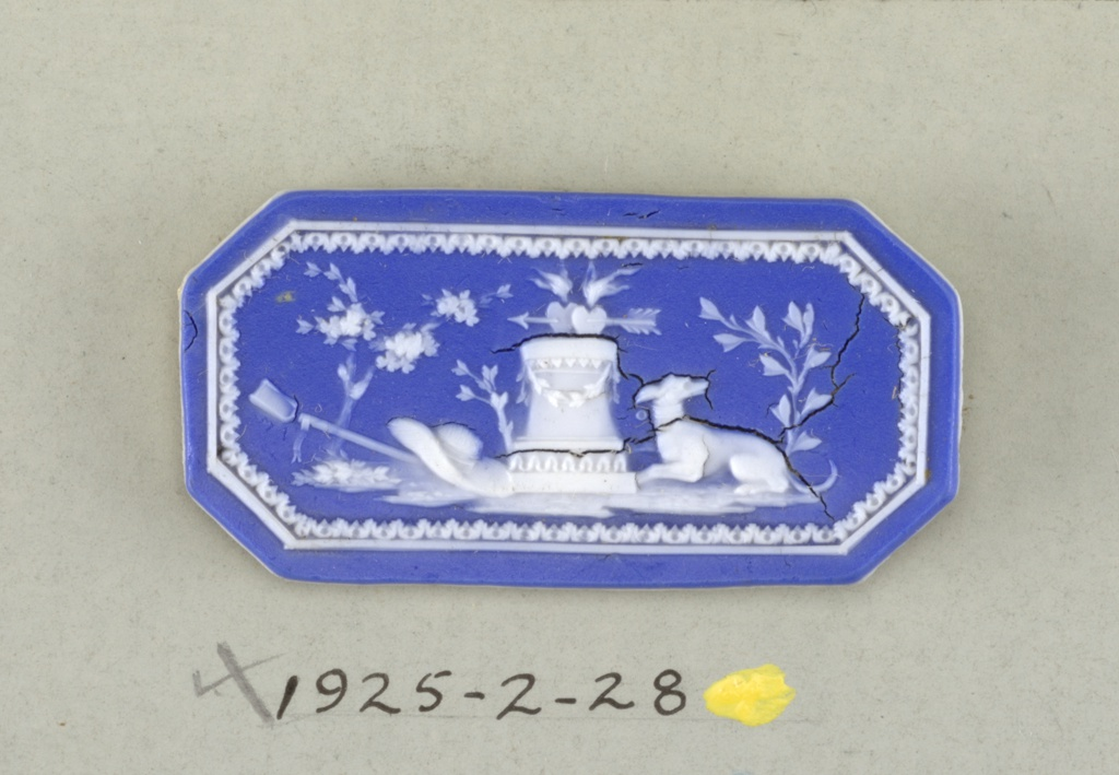 Octagonal mount in the style of Wedgwood Jasperware; dog and garden implements beside pedestal on which are two hearts pierced with arrow and love birds; border; white on blue ground.