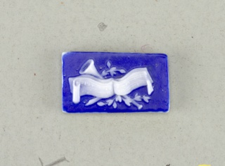 Two rectangular mounts in the style of Wedgwood Jasperware; ornamented with love birds, quiver of arrows, torch and leaves; on reverse, music scroll with horns and leaves; white on blue ground.  On card 4