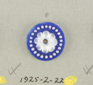 Circular medallion in the style of Wedgewood Jasperware; open flowers with twelve rounded petals surrounded by ring of dots; white on blue ground; central hole.