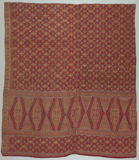 "Red silk brocaded cloth (kain songket) with all-over geometric pattern of stars and rosettes in gold brocade, with wide panel at one end showing the ""tumpal"" motif (row of isosceles triangles). Geometric border in gold."