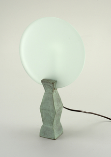 A bronze disc-shaped base, plastic cylndier, and glass shade.