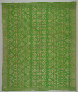Skirt cloth made of two lengths seamed down long sides of bright green silk cloth with scaled design in gold thread. Design shows long stemmed stylized floral forms extending into center of skirt at right angles from long side borders (8cm) which are filled with various diamond repeats with fret guard strips. Narrow borders at ends of skirt show stylized flower and leaf forms with geometric guard strips. Wide white cloth selvedge on border side of each length and narrow green cloth selvedge on opposite side of each length.