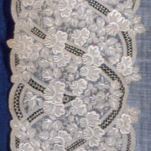 White on white embroidered handkerchief with wide floral borders and a plain center. Some openwork details.