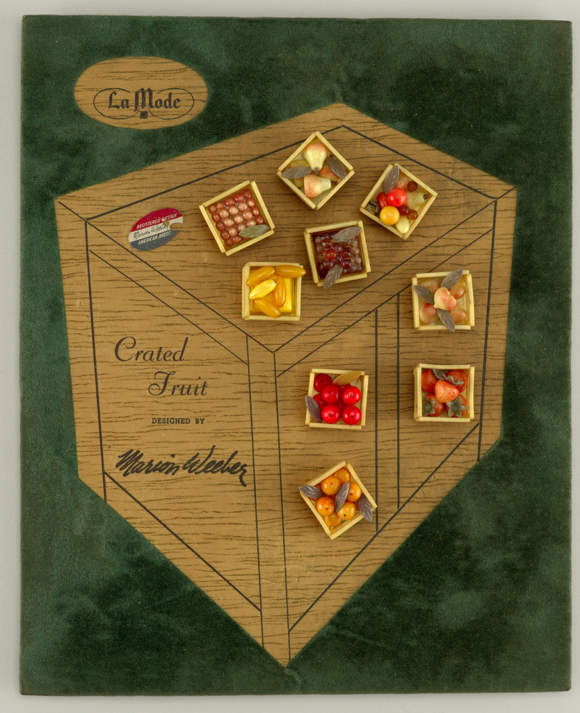 "Upright rectangular brown cardboard with cut out of crate in green felt; 9 square buttons  are attached to cardboard, each with a different fruits.  printed on left hand corner La Mode [logo]; printed center left  "" Crated Fruit"" / ""designed by  Marion Weeber""."