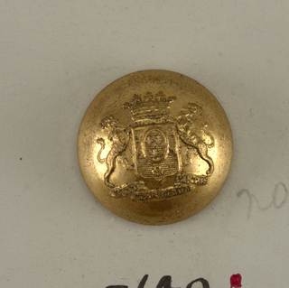 "Circular, convex button with ornament showing shield with heraldic devices, lion supporters, crown above and below, a ribbon with ""vicit iter durum pietas."" Brass back and shank. On reverse: ""G and Cie Paris"", 18 in shield, small coat of arms impressed.  On card E"