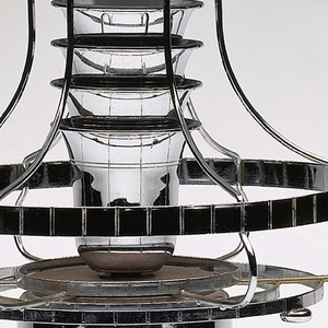 """Base of lamp (a) made from recycled base of electric """"Osterizer"""" blender, a tapering, stepped, circular form, surmounted by cage made of wire from recycled electrical object (fan?); central structure made of four nested metal cups; shade (b) at top, formed of circular stepped, domed pan with plastic finial in center. All parts highly polished chrome. Standard white electrical cord and plug."""