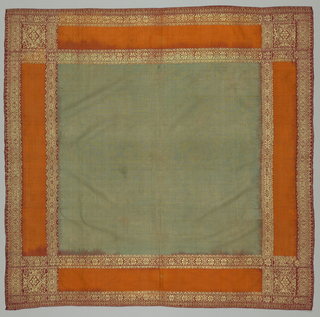 Green ground is surrounded by guard borders of orange rectangular bands and red squares in each corner. Guard borders are heavily embellished by gold thread in a predominantly geometric pattern.
