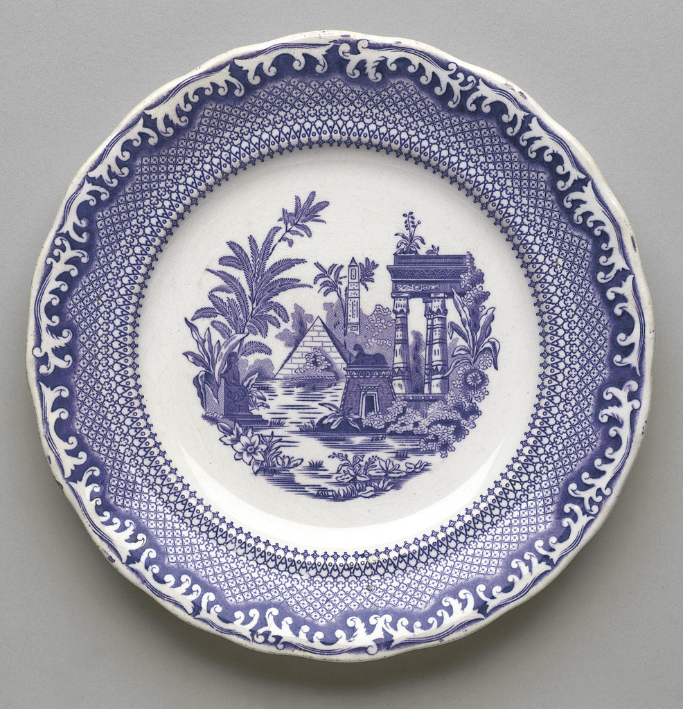 A white plate with a blue decorative border, and an Egyptian scene in the center.