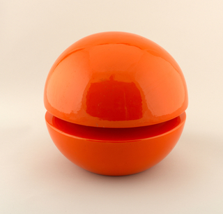 Lamp with spherical form, created with two molded hemisperes. Horizontal central division between hemisperes filled with circular fluorescent tube, inset deeper into center. Hemispherical sections glazed overall in brilliant orange. Base of lamp with metal plate. Fitted with electrical cord, plug, and switch.