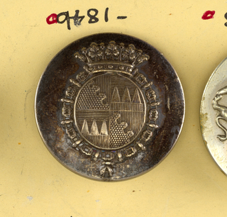 "Slightly convex button with heraldic devices, encircled by a chain and surmounted by a crown. Back and shank of brass. On reverse, ""Dagbert and Matheissen Place Beauvau.""  On card C"