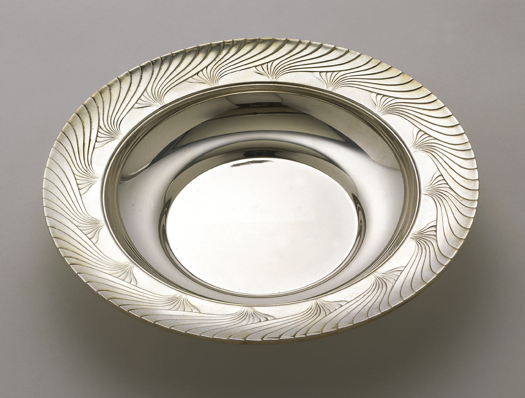 A silver bowl with a wide patterned rim.