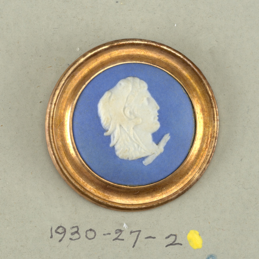 Rounded medallion showing classical head (man's) in style od Wedgwood Jasperware (white on blue ground) mounted as a button with metal rim, back and shank.