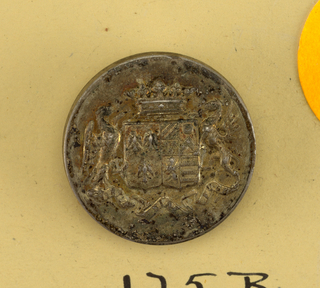 Flat button with ornament showing double shield with heraldi devices, eage and gridde supporters, a crown above and below, a ribbon with writing on it. Brass back and shank.  On card C