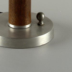 Round aluminum base, cynlindrical wood body, aluminum dome shade, and circular wood finial.