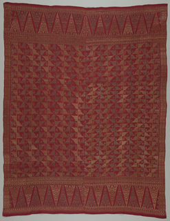 "Two lengths of woven fabric sewn together with silver and gold patterns on red ground. Field covered with stripes patterned by toothed or dove-tailed triangles. Bordered on all sides by geometric pattern and features ""tumpal"" motif (row of isosceles traingles) at sides."