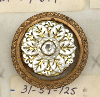 Circular button of bronze with central ornament of pearl shell carved to represent flowers with rhinestone center.  On card 28
