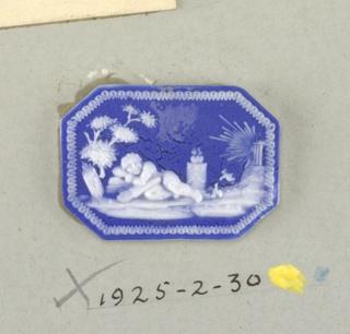 Octagonal mount in the style of Wedgwood Jasperware; cupid sleeping under tree; white on blue ground.
