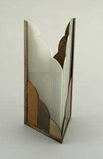 V-shaped glass volume sits in base formed of multiple metals; open to the top with scalloped edges and parralellogram plan.