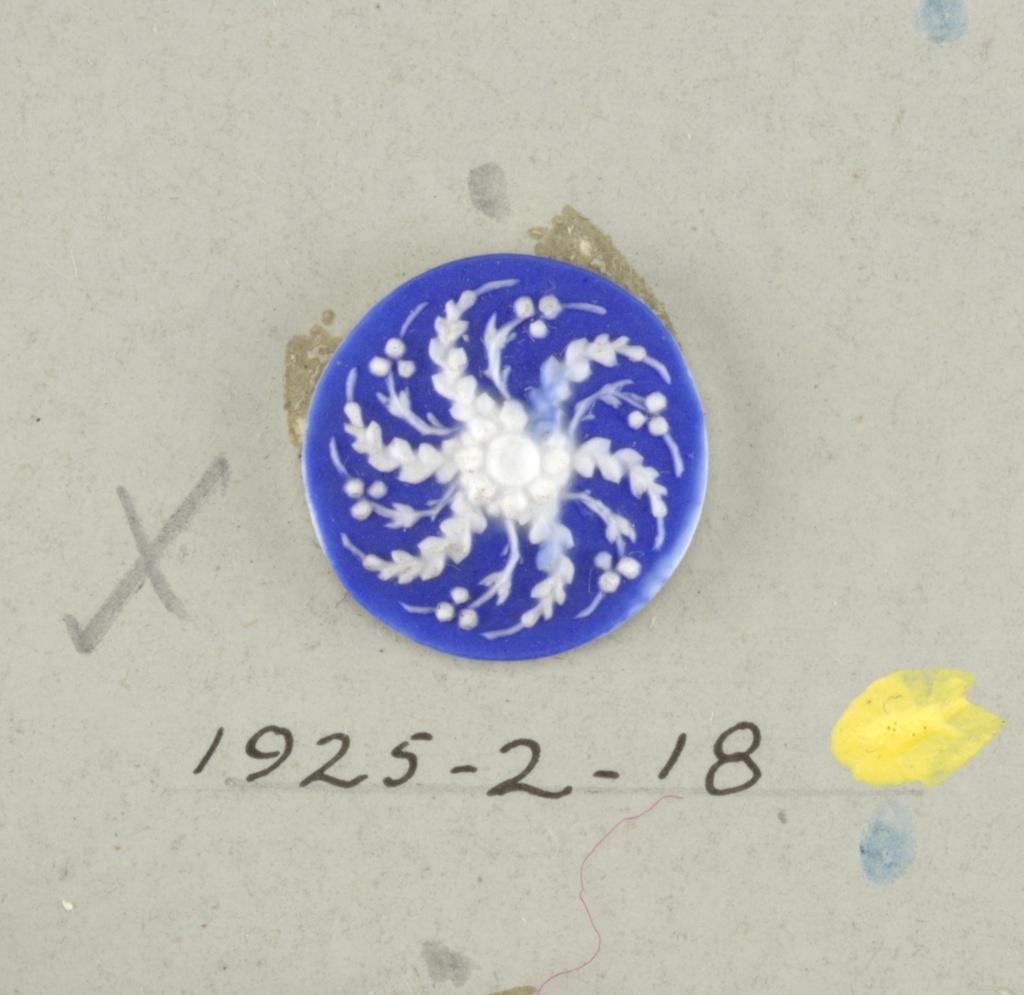 Circular medallion in the style of Wedgwood Jasperware; open flower swirled leaf ornament; white on blue ground.  On card 4