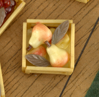 Button in the form of an open-topped wooden crate containing four pears in tones of yellow to pink, with two narrow green leaves interspersed among them. Button mounted along with nine others witn different types of fruit, on card decorated with image of crate on a green ground.