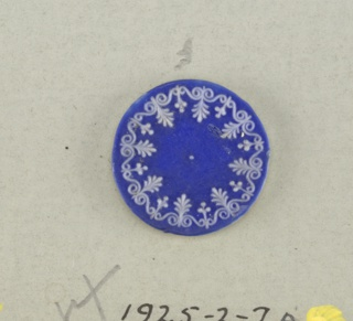 One circular medallion in the style of Wedgwood Jasperware; ornamented with anthemion-like form alternating with three-leaved form set within scrolls; white on blue ground; Central hole.