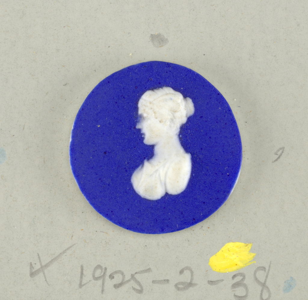 Circular medallion in the style of Wedgwood Jasperware; ornamented with bust in classic manner; white on blue ground.  On card 4
