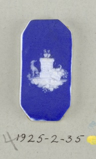 Octagonal mount in the style of Wedgwood Jasperware; ornamented with pierced heart on a pedestal with a dog and a basket of flowers at its base; white on blue ground.