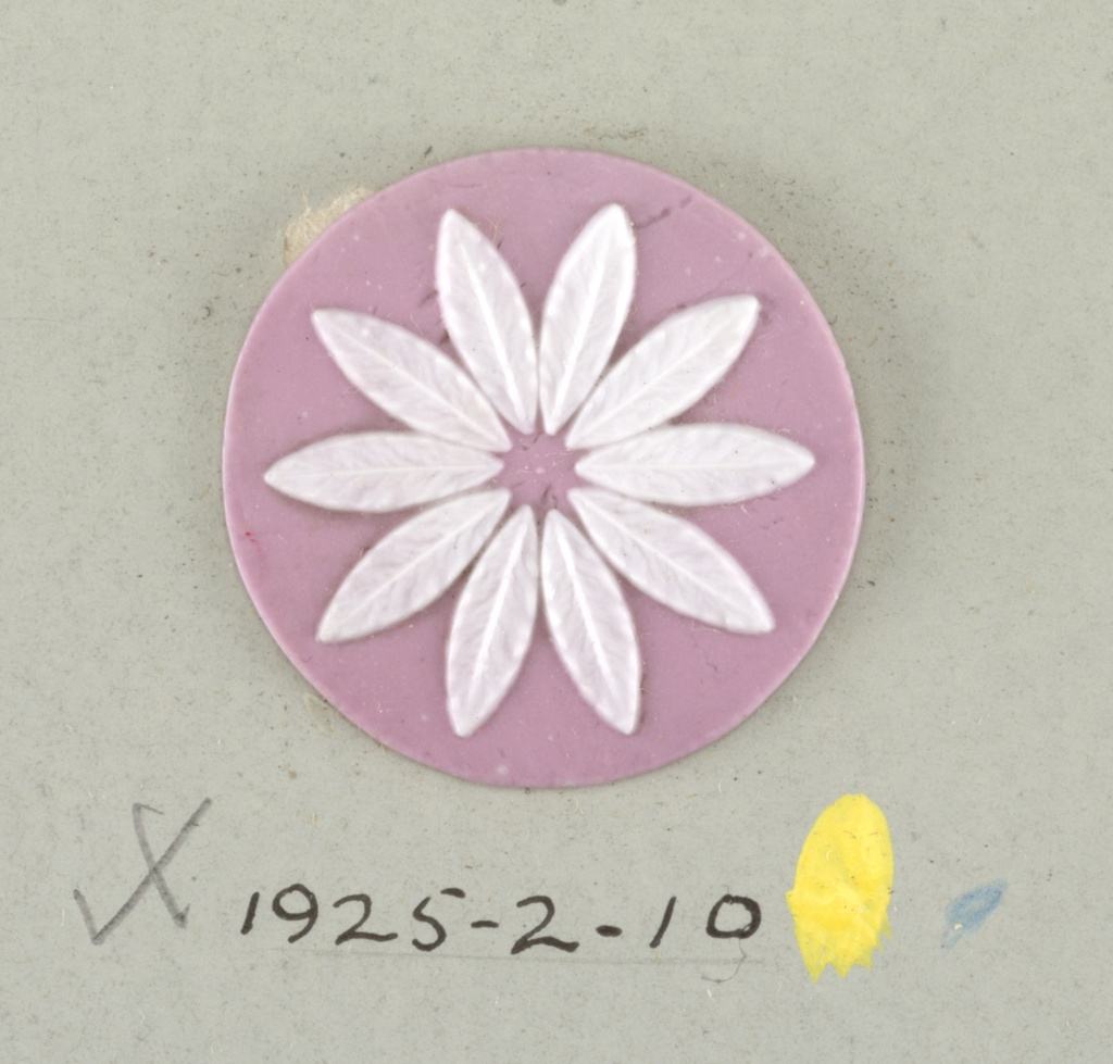 Circular medallion in the style of Wedgwood Jasperware showing a flower with ten petals; white on pink ground.  On card 4