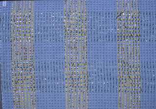 Horizontal and vertical bands forming a plaid design in light blue and yellow chenille and flat strips of gold and silver thread.