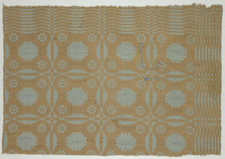 Single snowball pattern in tan and pale blue. Border on two sides suggests form of sunrise pattern. Plain cloth selvages on two short sides.