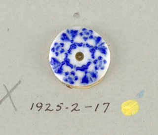Circular medallion in the style of Wedgwood Jasperware; showing four open flowers alternating with leaf ornaments and scrolls and dots; blue on white ground; central hole.  On card 4