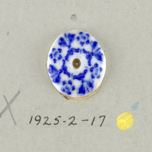 Circular medallion in the style of Wedgwood Jasperware; showing four open flowers alternating with leaf ornaments and scrolls and dots; blue on white ground; central hole.