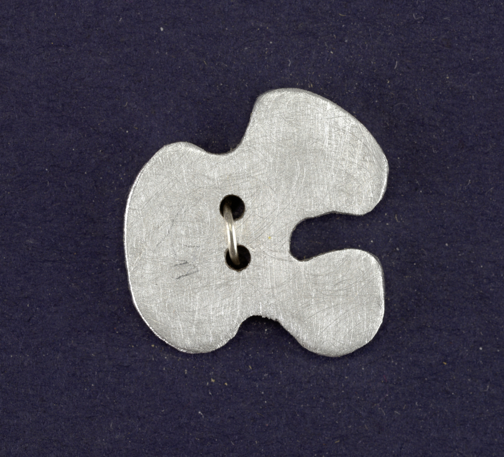 Flat irregular form pierced with two holes; matt surface.