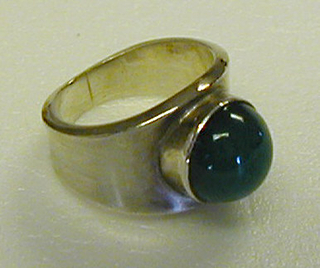 Plain silver band, narrow at bottom, wider at top, surmounted with bezel-set spherical, dark green onyx stone.