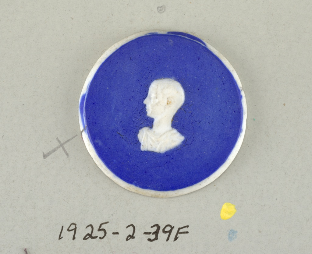 Six circular medallions in the style of Wedgwood Jasperware; each ornamented with a head drawn in the Classic manner; white on blue ground.  On card 4