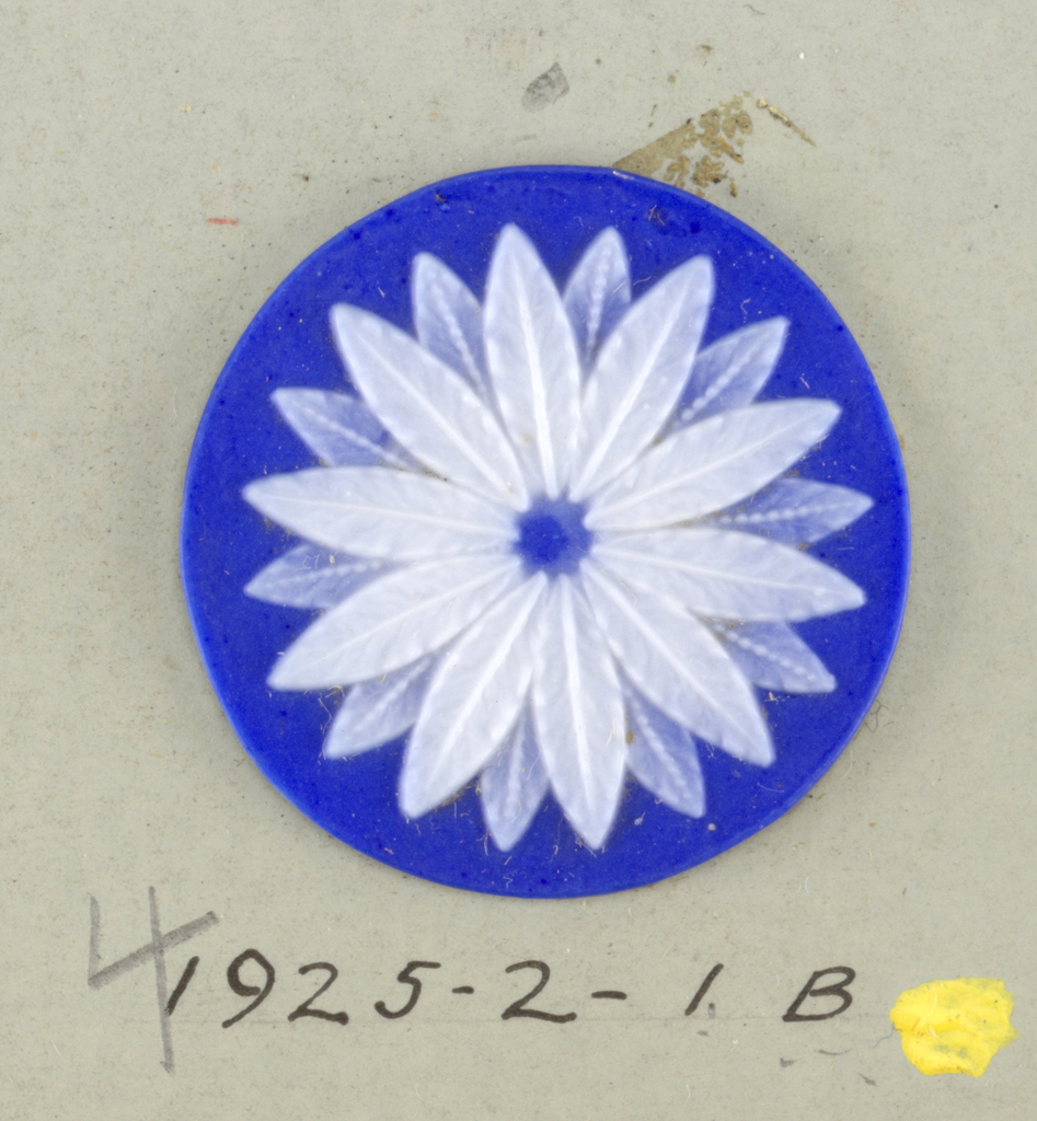 Medallions in style of Wedgwood Jasperware; a twenty-petaled white flower on blue ground. Central hole indicates they may have been intended for buttons.