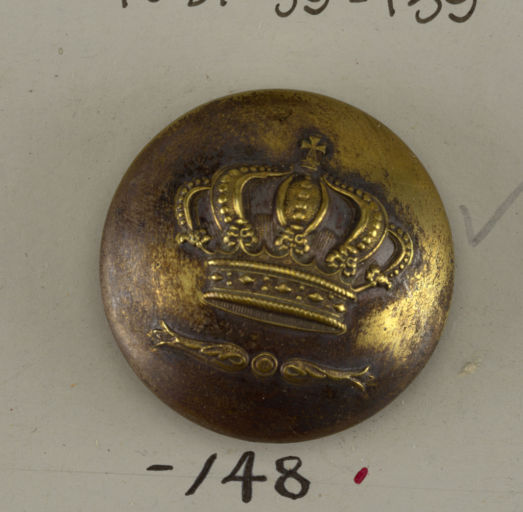 """Convex button with ornament of a crown over a motif of folded leaves with a dot between. On reverse: """"Moos Paris Bertelli Torion"""". Probably made for an Italian family.  On card E"""