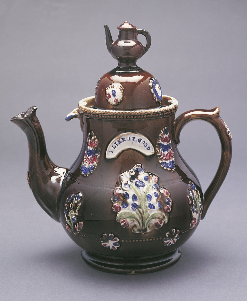"A brown teapot and dome lid decorated with a flower pattern. On the side, a white arch says: ""I Like it Good"". The knob on the lid a miniature teapot."