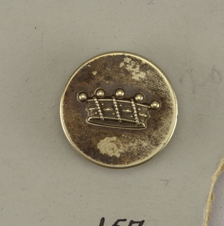"Flat button ornamented with a crown. Back and shank of brass. On reverse, ""G and Cie Paris M18"".  On card E"