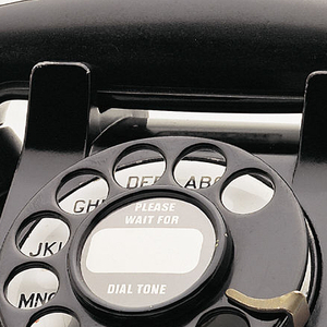 Black rotary telephone; transmitter/receiver handset in cradle on raised body with square base; black metal finger wheel above white dial with black numbers; smooth cord, one end attached to handset and the other to back of telephone base.