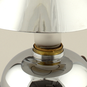 Globular base (a), with small circular brown Bakelite switch on side, accepts incandescent bulb; conical shade (b) clips to bulb.