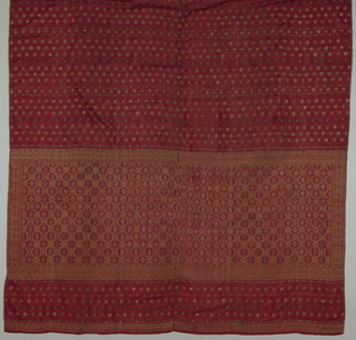 Textile, probably a sarong, of dark red ground with blue plaid all-over design showing small pattern of metallic embroidery. Wide border shows geometric lattice design.