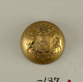 Circular, convex button showing shield with heraldic device, flanked by dogs, surmounted by a crown. Brass shank.  On card E
