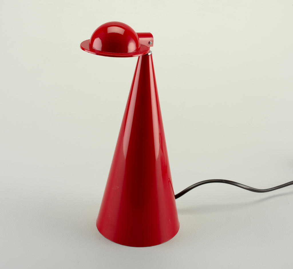 A solid red table lamp with a tall cone base and an attached bowl with rim to house the bulb.