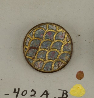 circular button, colored centers surrounded by gilded leaf forms; backs with channel for sewing on to cloth.  On card 10