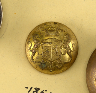 "Convex button with ornament showing heraldic devices on a shield, lion supporters, crown and above and leaf ornament below. Back and shank of brass. On reverse, ""Superfins Paris E.B.""  On card C"