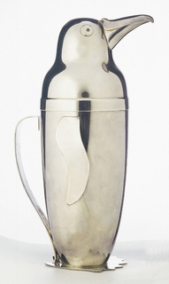Ovoid body (a) and cover (b) in the form of a standing penguin with flat wings applied at sides, and flat base in form of feet; strap handle at back.  Cover (b), in the form of penguin's head and shoulders, with hinged beak as spout.