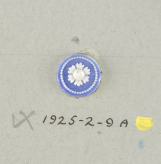 One circular medallion in the style of Wedgwood Jasperware; ornamented by open-faced flower surrounded by ring of small white dots; white on blue ground; the flowers vary slightly with six rounded petals. Central hole.